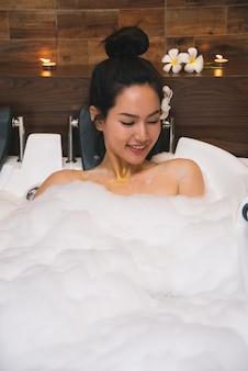若い美しいアジアの女性は泡風呂を取る