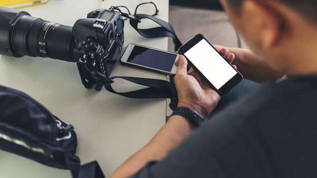 写真家の男の手を保持し、スマートフォンや携帯電話を使用して