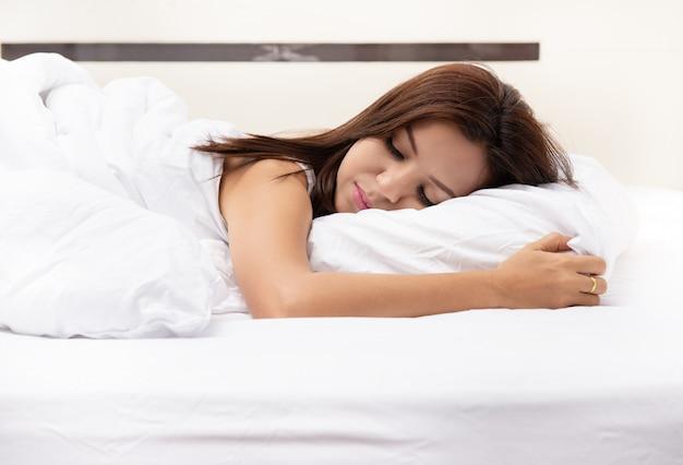 白いベッドで寝ている美しい若いアジア女性