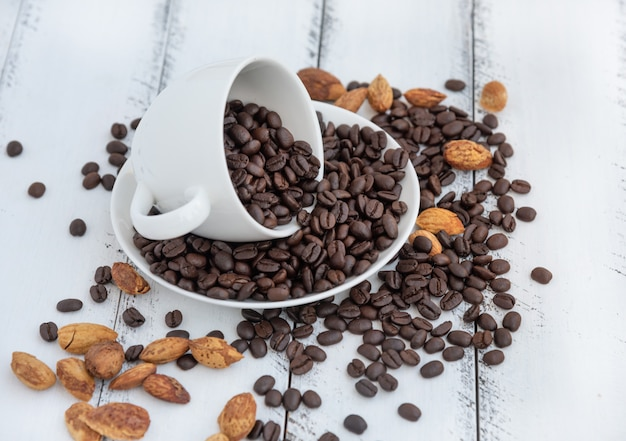 白い木のコーヒーの白いカップで焙煎したコーヒー豆の山