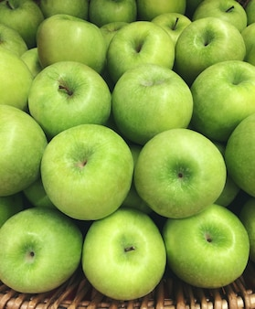 Свежая бабушка смит или золотые вкусные зеленые яблоки в корзине