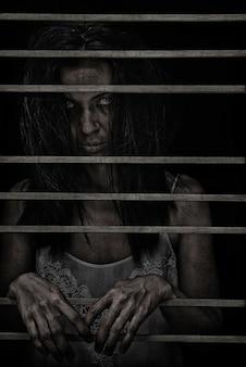 黒の暗いケージのポンドルームで所有している女性のホーストハロウィーンのホラーシーン