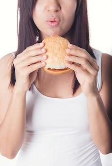美しいアジアの女性は、白いバーガーを食べる