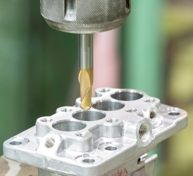 マシニングセンタで自動車部品を加工するオペレータ