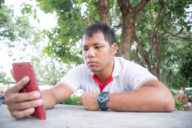 アジア人男性は、携帯電話で退屈で悲しい瞬間を感じています。彼はモバイルから何かを待っています。