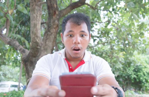 アジア人の男性が公園で携帯電話でショックと驚きの瞬間を感じる