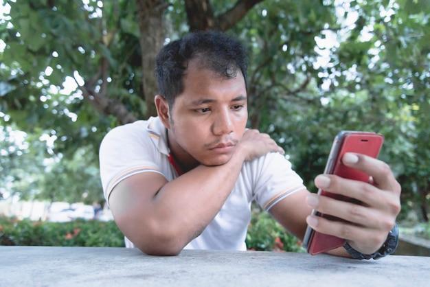 アジア人男性は、携帯電話で退屈で悲しい瞬間を感じています。
