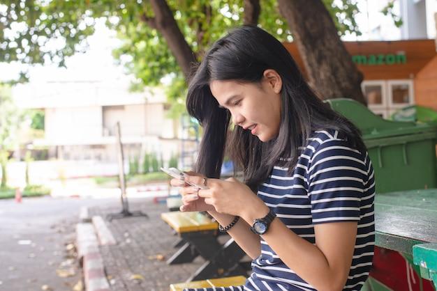 Азиатские женщины загорают кожа с мобильным телефоном в парке. она выглядит счастливой. концепция задачи. концепция телефона наркоман. наружная работа. концепция свободного времени. копировать пространство