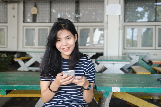 Азиатские женщины будут улыбаться, играя в мобильный телефон.