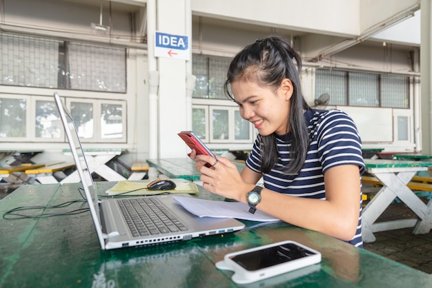 アジアの女性は、大学周辺のテーブルで携帯電話とノートブックを使用しています。彼女は仕事に満足しているようです。ソーシャルメディア中毒者の概念。