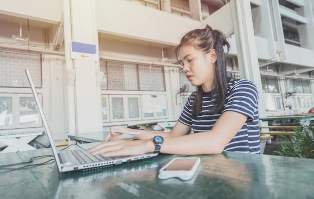 アジアの女性は、大学地区のテーブルの上のノートブックで作業しています。彼女はストレスと穏やかな仕事を見ています。