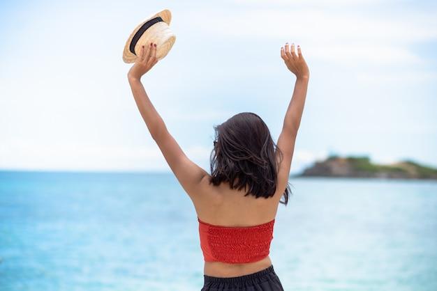 ピンクのタンクトップを着ている背中の女性の日焼けした肌は、立っている腕を空に伸ばして麦わら帽子をかぶっています。海と新鮮な空を眺めています。