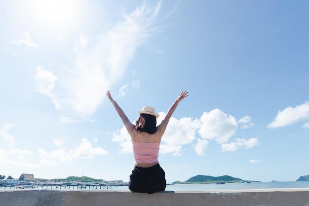 アジアの女性の日焼け肌ピンクのタンクトップとモルタルの上に座って麦わら帽子をかぶって