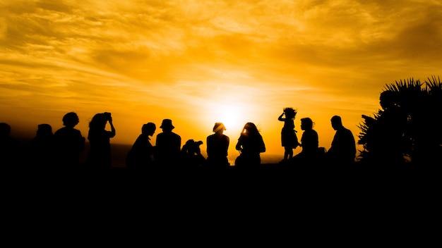 視点で夕日を見ている多くの人々をシルエットします。