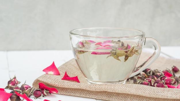 白い木製のテーブルに紅茶ピンクのバラの花が咲いた。