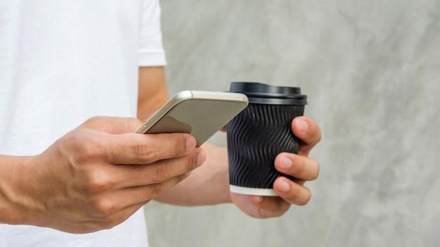 スマートフォンを使い、コーヒーを飲む男性。