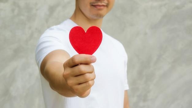灰色の背景に赤いファブリックの心臓を保持している男性。