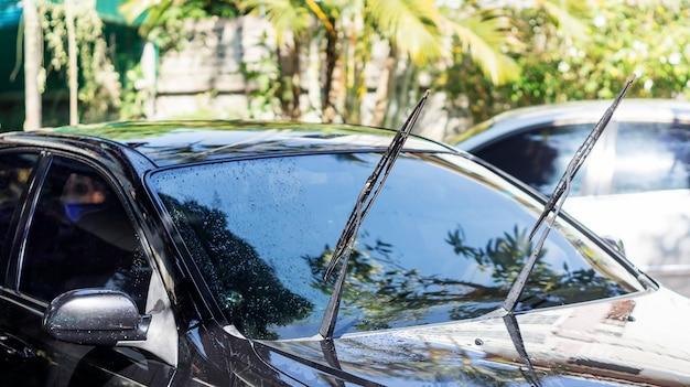 黒い車を洗う人。