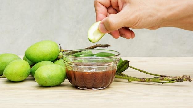 木製のテーブルの上の甘い魚醤とグリーンサワーマンゴー(生マンゴー)。