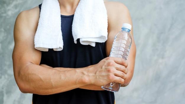 水のボトルを保持している男。