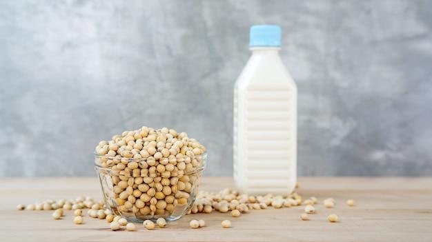 ボウルに大豆と木製の背景に豆乳。