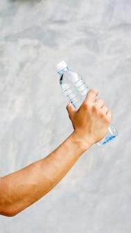 Мужчина держит бутылку воды.