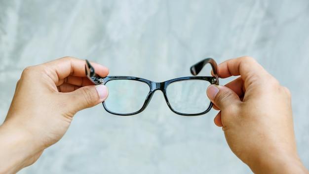 灰色の背景にメガネを抱きかかえた。
