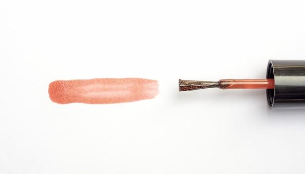 Коричневый лак для ногтей на белом фоне.