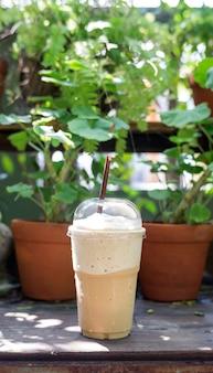 木製のテーブルと植物の背景にコーヒースムージー。
