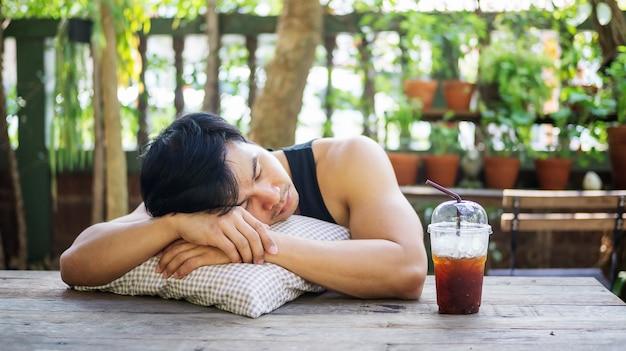 Молодой азиатский человек спать в саде.