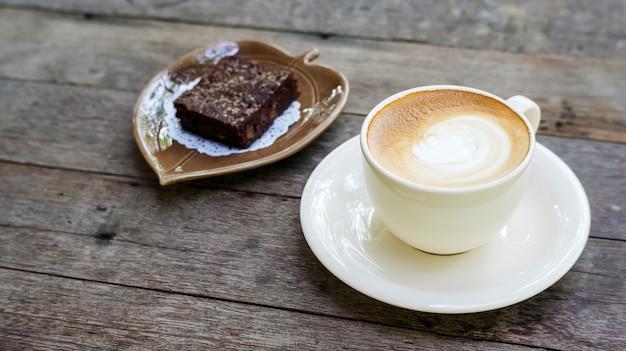 ホットコーヒーとブラウニーケーキの木製のテーブル。