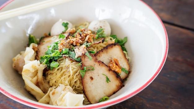 木製の背景(タイの麺)に豚肉の麺。