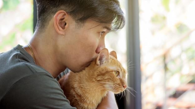 赤い猫を抱えている男たち。