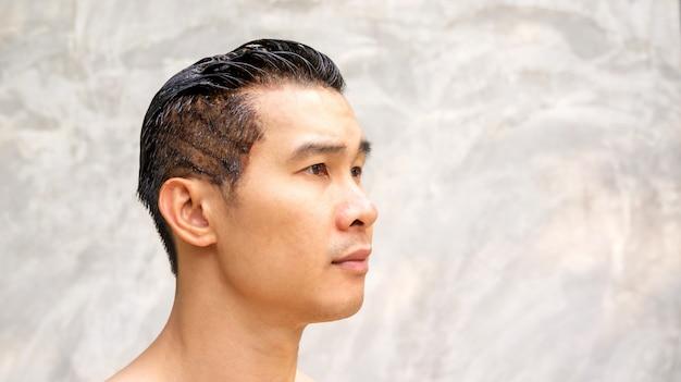 アジアの男性は、灰色の背景に彼の髪の色を染めます。