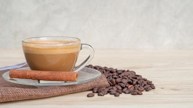 Чашка горячего кофе и корицы на деревянном столе.