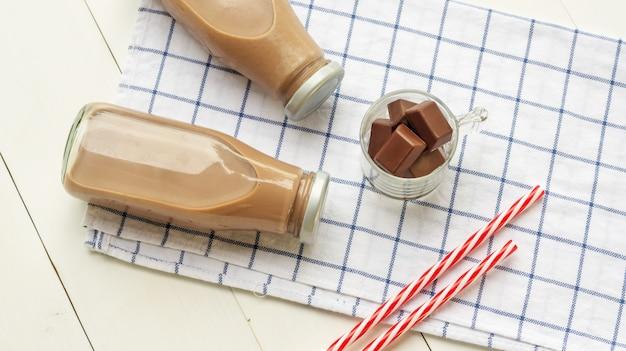 白い木製のテーブルの上のチョコレートミルク。