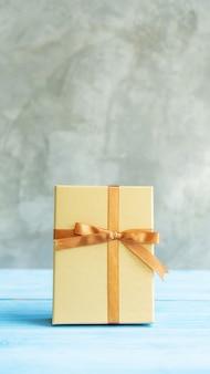 青い木製のテーブルの上の金のギフトボックス。