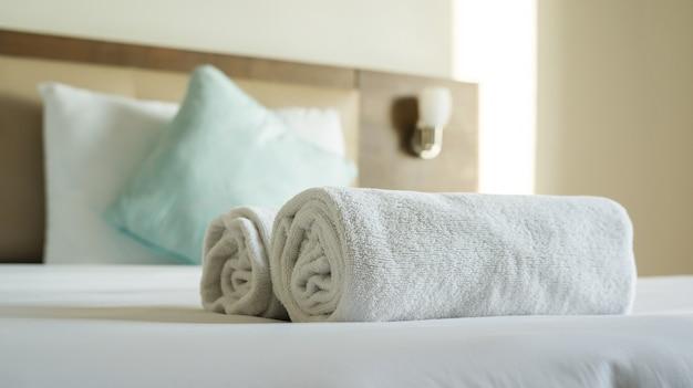 ベッドに白いタオルシャンプーと石鹸。