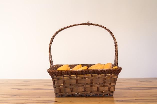 ヴィンテージのテーブルの上のバスケットにマンゴー