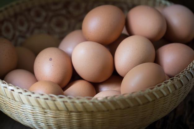 木製のテーブル背景にバスケットの卵のクローズアップ