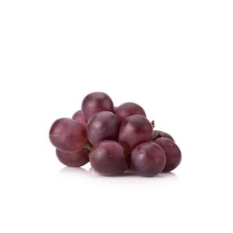 Спелый красный виноград с листьями на белом