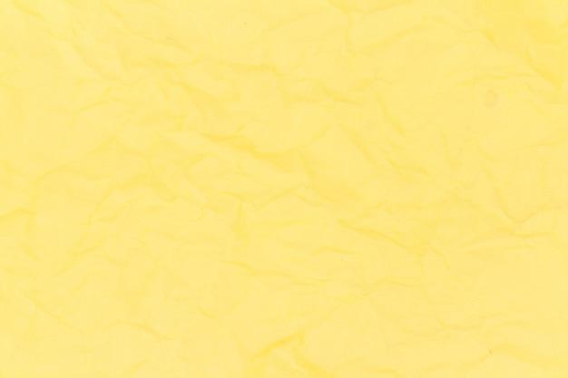 黄色のしわくちゃの紙のテクスチャ背景