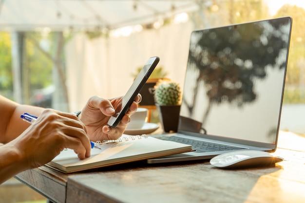 携帯電話を使用して、テーブルの上にペンでノートに書いているビジネスマン。