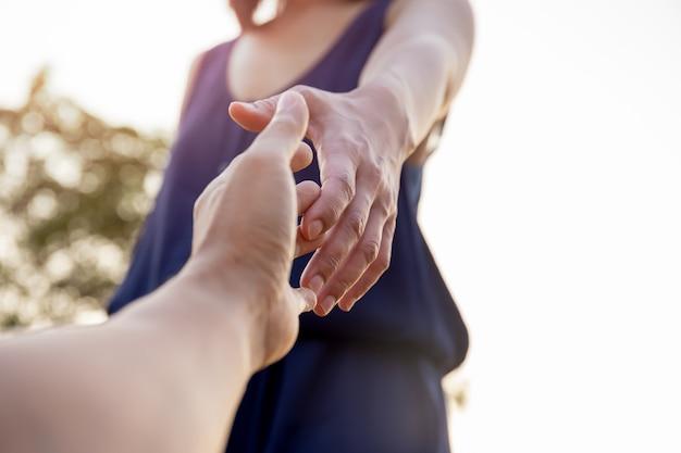 女性の手がお互いに助けを求めて手を差し伸べる。