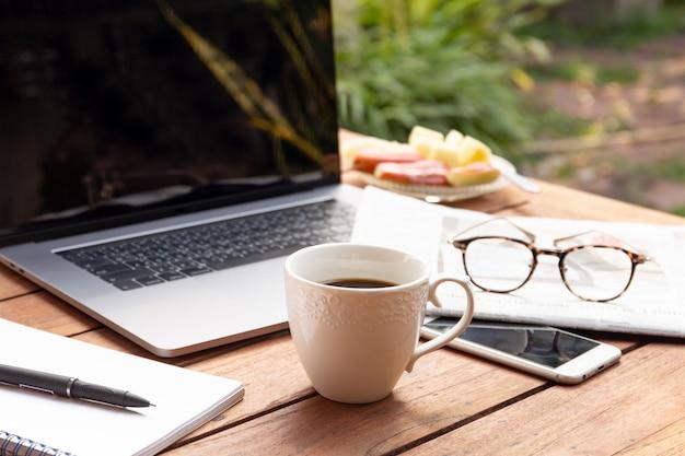 ノートパソコン、メガネ、新聞のコーヒーマグカップビジネスオブジェクトの概念。