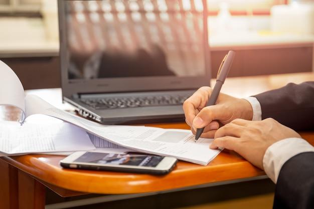 ビジネスマンのラップトップに取り組んで、紙のノートに書いています。