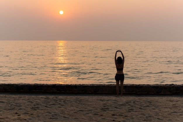 Женщина делает йогу на закате на пляже в отпуске.