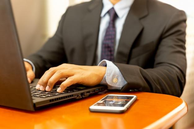 実業家の手が木製の机の上の携帯電話でキーボードのラップトップに入力します。