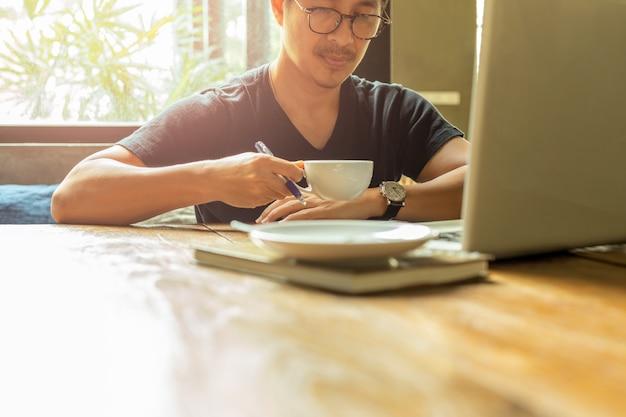 Человек портрета азиатский при стекла имея перерыв на чашку кофе работая с компьтер-книжкой.