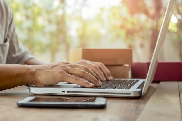 男の手がテーブルの上の小包パッケージ配達とノートパソコンのキーボードで入力します。